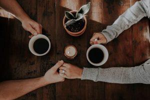 コーヒーカップ、相談、手を取り合う